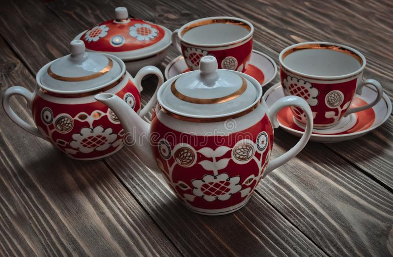 古色古香的套陶瓷茶壶,杯子,在一张木桌上的茶碟 免版税库存图片