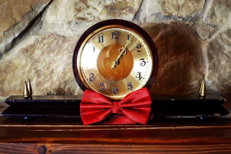 古色古香的木时钟和红色蝴蝶新郎的石背景的,新郎的早晨,婚姻的辅助部件 库存图片