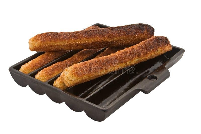 古色古香的玉米面包平底锅棍子 免版税库存照片