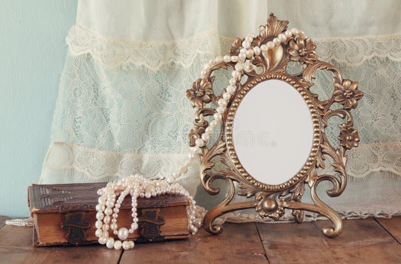 古色古香的空白的维多利亚女王时代的样式框架和旧书与葡萄酒成珠状项链在木桌上 减速火箭的被过滤的图象 库存照片