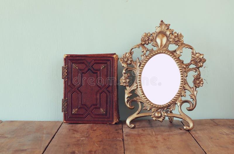 古色古香的空白的维多利亚女王时代的样式框架和旧书在木桌上 减速火箭的被过滤的图象 模板,准备投入摄影 免版税库存照片
