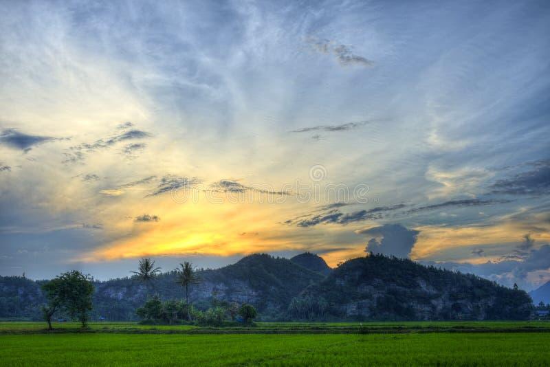 古色古香的美丽的风景云彩和小山用绿色植物报道日落&树、橙色阳光、蓝色白色和灰色天空 免版税库存照片