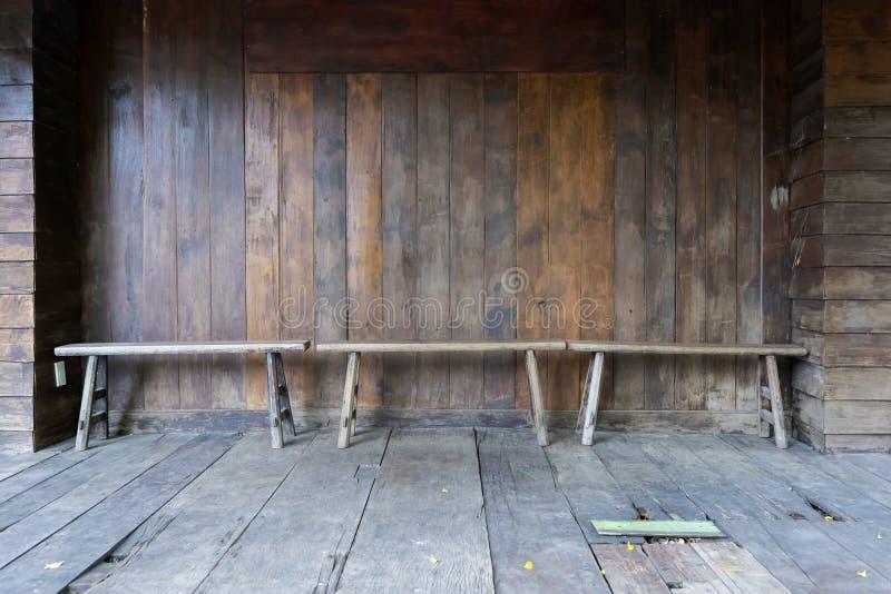 古色古香的老长的木椅子和背景木上的墙壁 库存照片