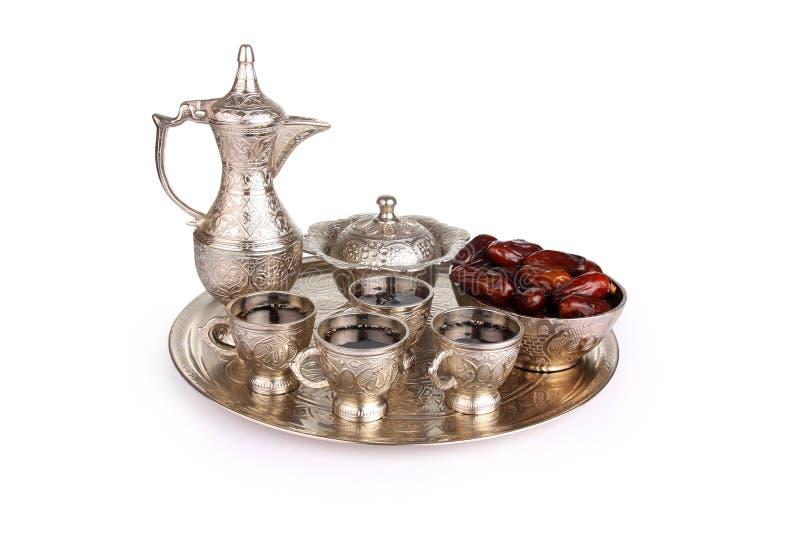 古色古香的银色投手和咖啡杯设置了与在盘的日期 库存图片