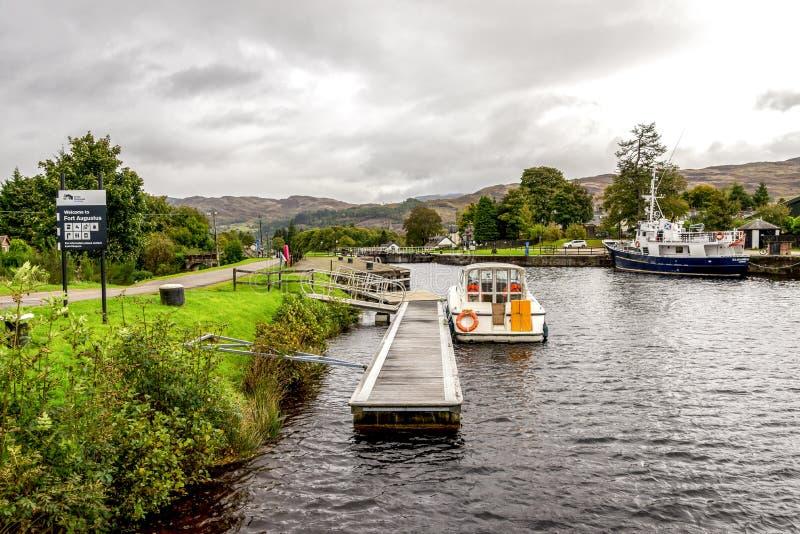 古苏格兰运河看法有在从奈斯湖入口,堡垒奥古斯都,苏格兰的锁附近停放的两三条小船的 免版税库存照片