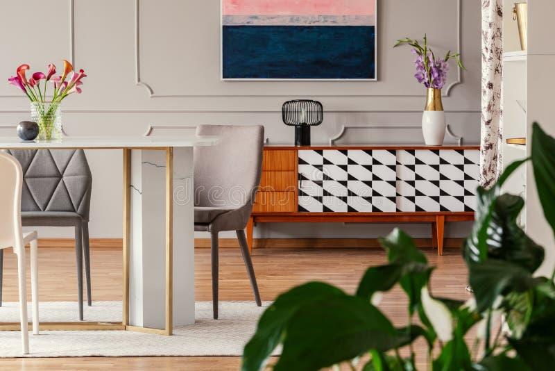 古董、木餐具柜与样式和用餐椅子在一间艺术性的公寓屋子的一张大理石和金黄桌附近 免版税库存图片