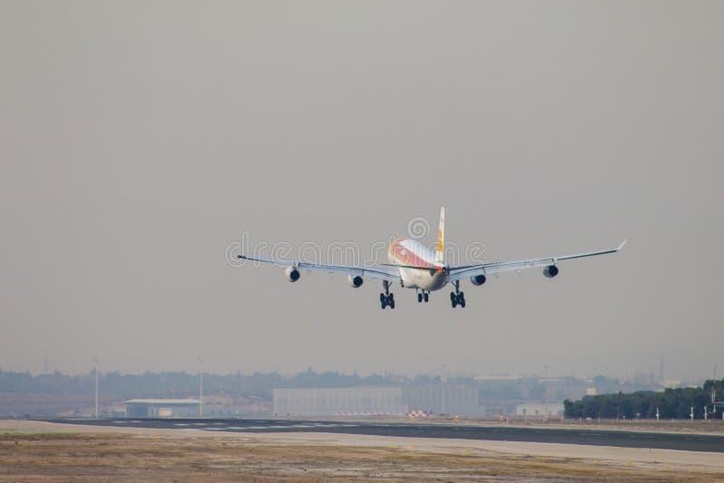 古西班牙喷气机对土地的班机方法马德里机场跑道的,看见从后面 免版税库存图片