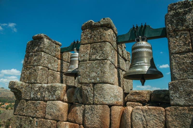 古铜色响铃特写镜头在石砖墙顶部的 库存照片