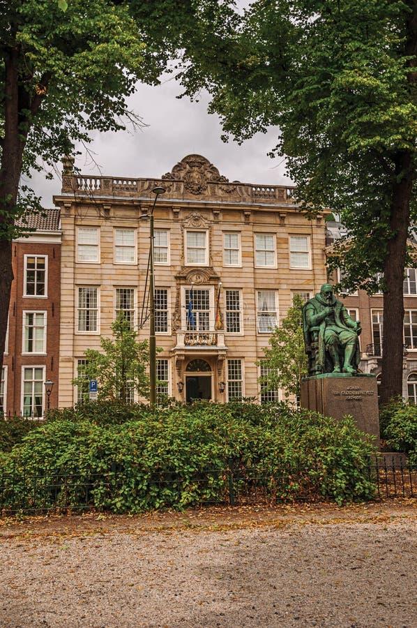 古铜色雕象、庭院有叶茂盛树的在砖瓦房前面和多云天空在海牙 免版税库存照片