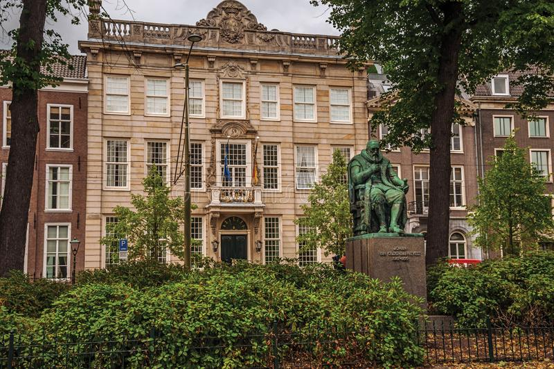 古铜色雕象、庭院有叶茂盛树的在砖瓦房前面和多云天空在海牙 库存照片