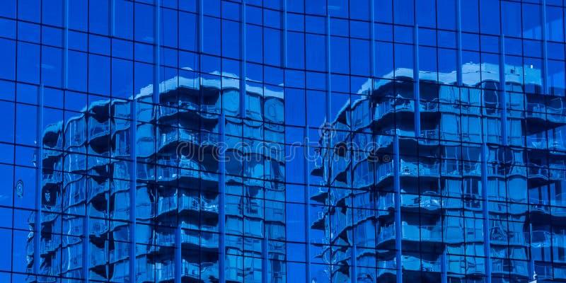 另一栋建筑窗户上蓝色高楼的反映 免版税图库摄影