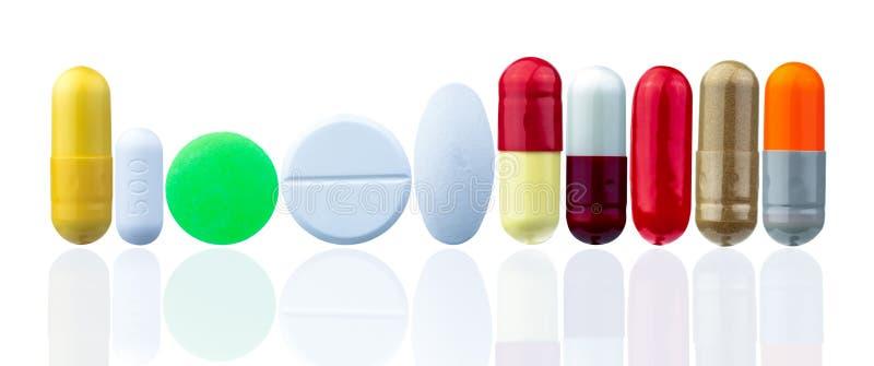 另外在与美好的样式的白色背景隔绝的药片大小和形状 黄色,绿色,白色,红色,橙色,金子 免版税库存照片