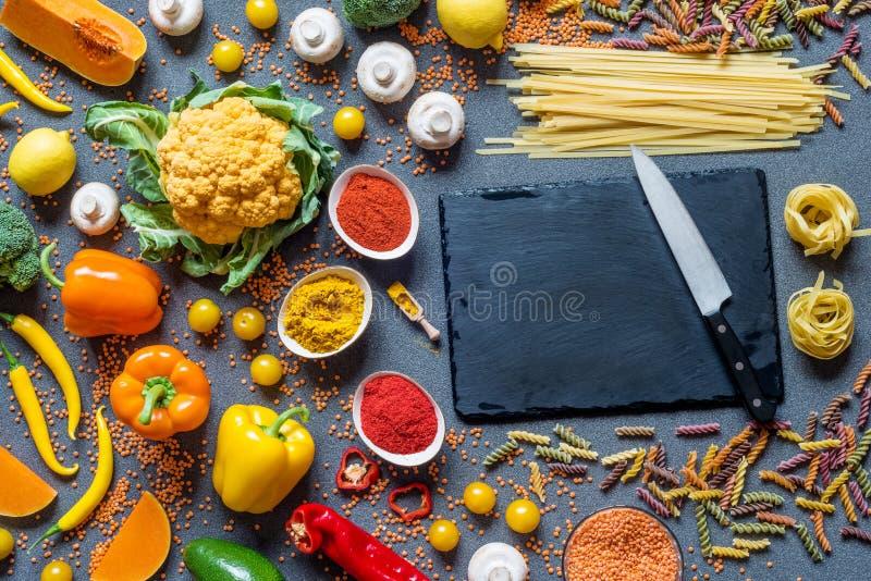 另外新鲜的五颜六色的菜、意粉和意大利细面条,香料 烹调的健康未加工的素食主义者成份在灰色 图库摄影