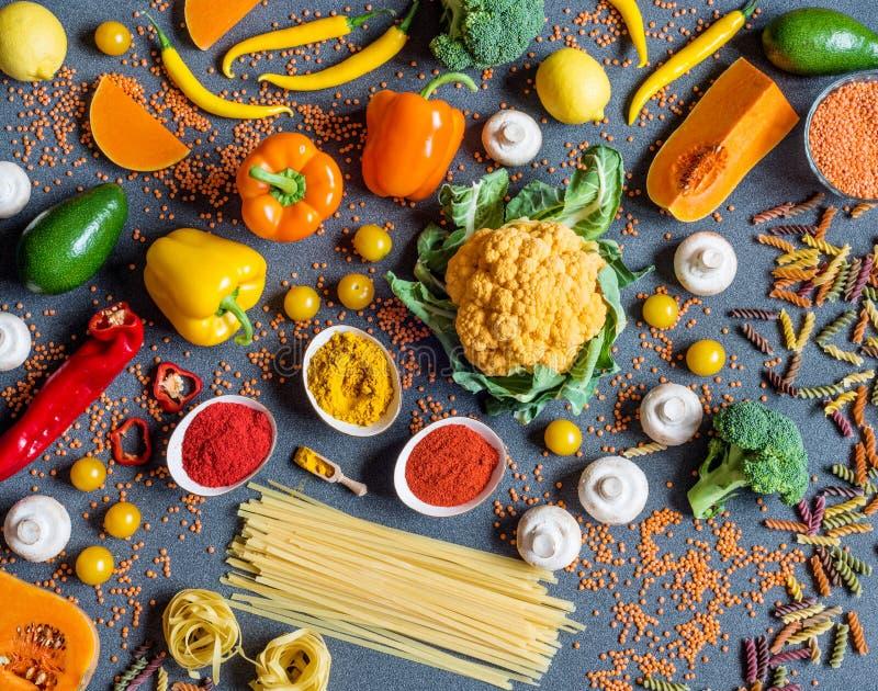 另外新鲜的五颜六色的菜、意粉和意大利细面条,香料 烹调的健康未加工的素食主义者成份在灰色 免版税库存照片