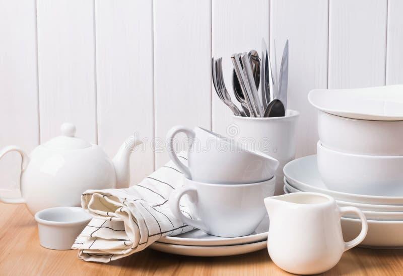 另外碗筷,板材,站立在白色木墙壁附近的杯子 免版税库存图片