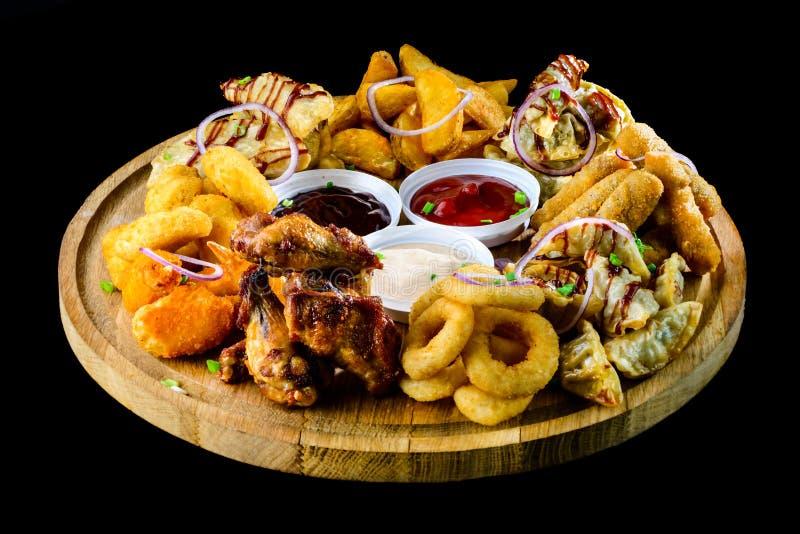 另外种类在木板的快餐在黑暗的backgrou 免版税库存照片