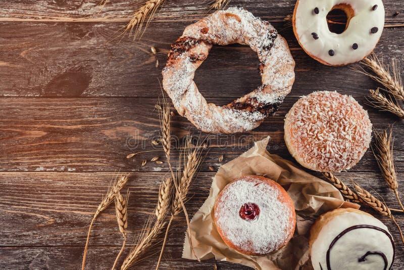 另外种类的分类谷物面包店:油炸圈饼和脆煎肉片在老木背景 免版税库存照片