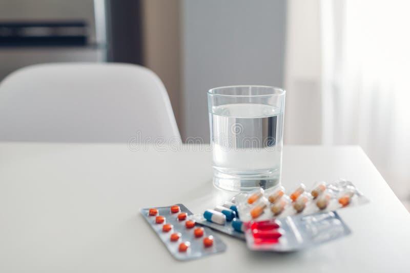 另外药片和杯在厨房用桌上的水 关心眼睛医疗保健卫生学医学 免版税库存图片