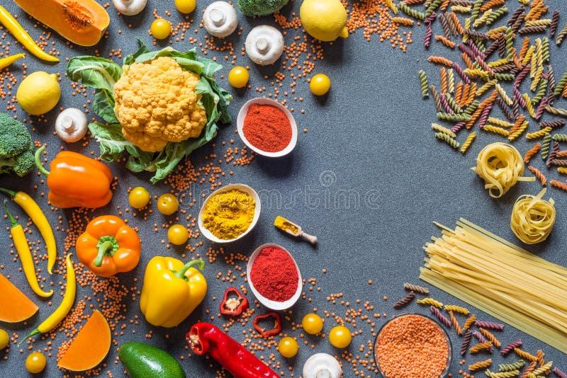 另外菜、意粉和意大利细面条,香料 烹调的健康未加工的素食主义者成份在灰色背景 免版税库存图片