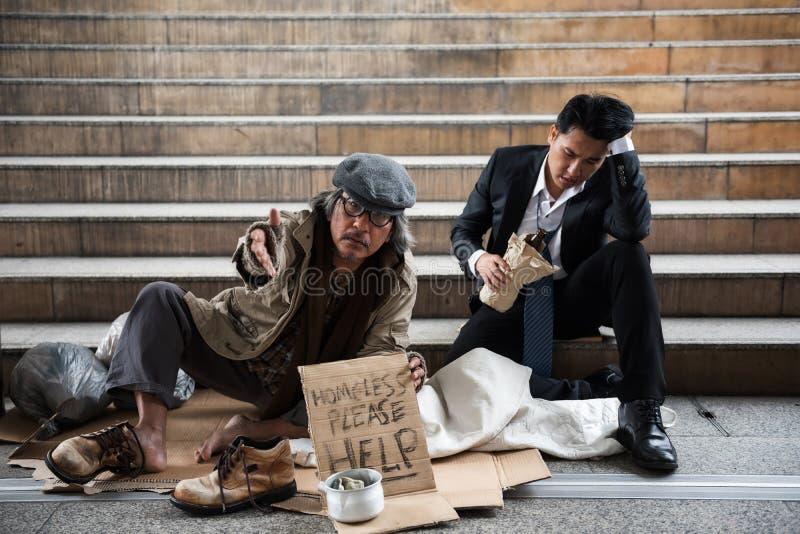 叫化子老人和醉酒的商人在镇里 库存照片