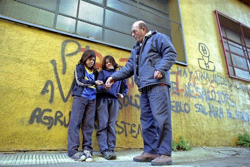年轻叫化子从街道工作者得到金钱 库存图片