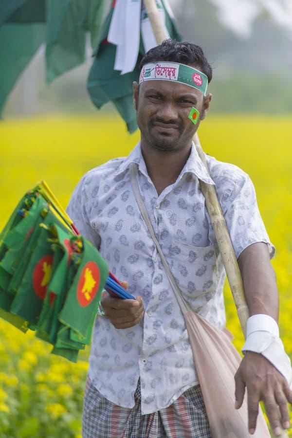 叫卖小贩卖孟加拉国的国旗在芥末领域在Munshigonj,达卡,孟加拉国 库存图片