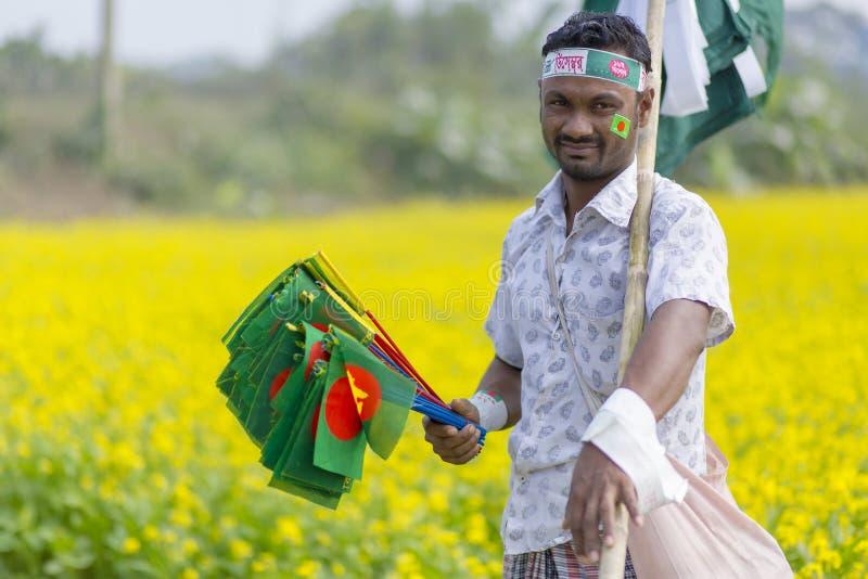 叫卖小贩卖孟加拉国的国旗在芥末领域在Munshigonj,达卡,孟加拉国 免版税图库摄影