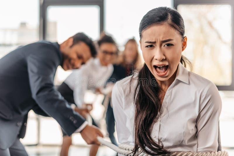 叫喊亚裔女实业家跳起与拉扯她的绳索和买卖人 图库摄影