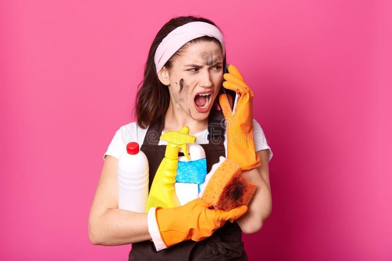 叫喊的妇女的图象发表演讲关于手机,当在家时清洗,穿戴了T恤杉、围裙和发带,深色的夫人 免版税库存图片