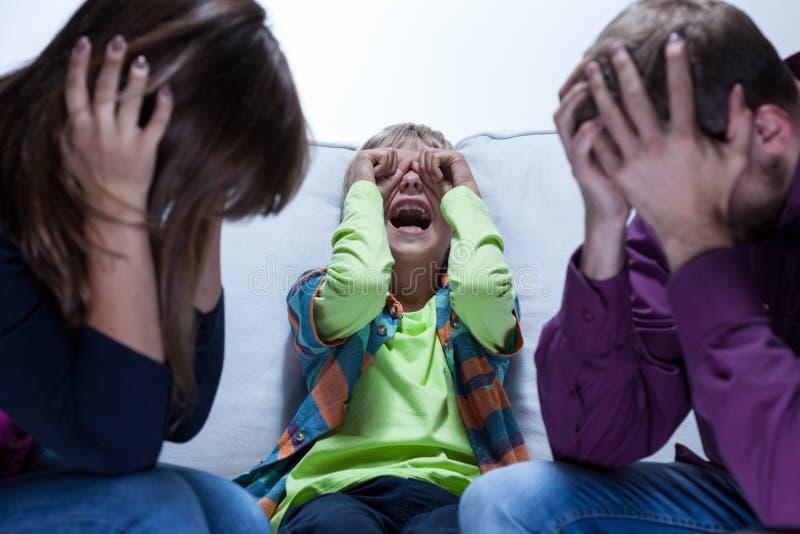 叫喊的男孩和疲乏的父母 免版税库存图片