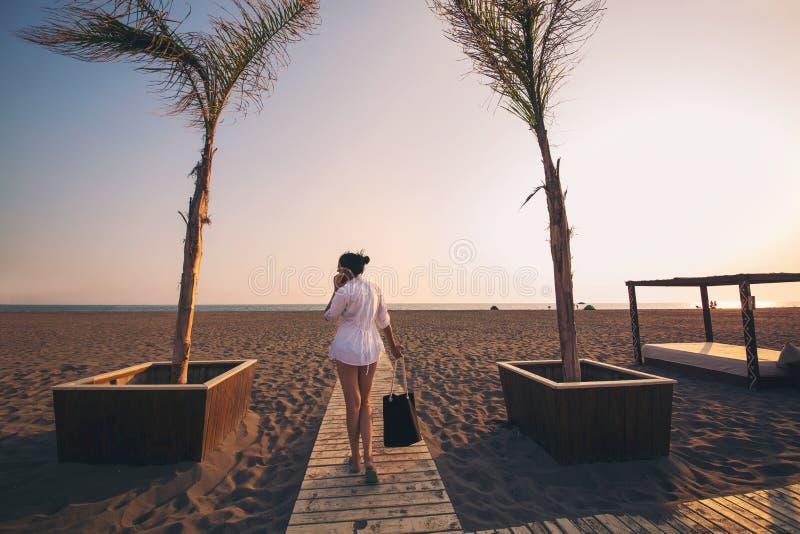 叫由电话和走在海滩的妇女 免版税库存图片