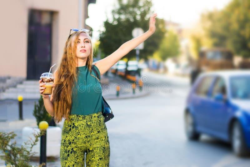 叫的女孩在街道上的出租汽车 库存图片