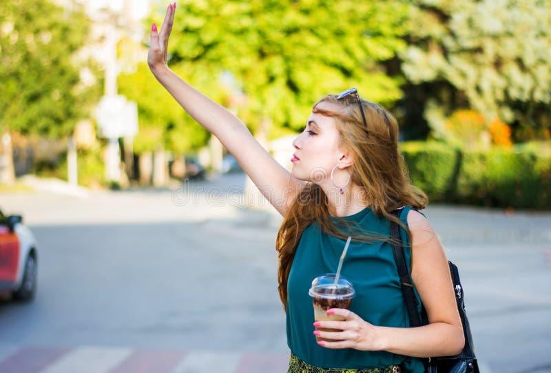 叫的女孩在街道上的出租汽车 图库摄影