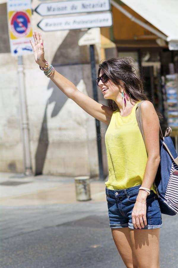 叫美丽的少妇在街道上的出租车 库存图片