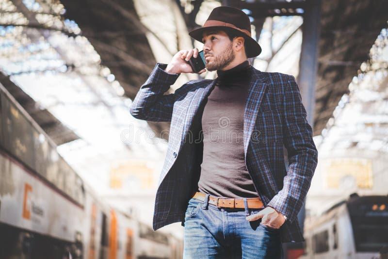 叫英俊的典雅的年轻西班牙的人在他的手上拿着巧妙的电话和,当站立在铁路时的他 库存图片