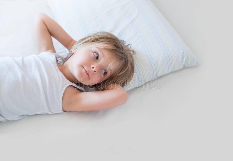叫醒微笑在父母` s床上的愉快的女孩女儿对早晨 与孩子的愉快的轻松的家庭生活在家 免版税库存图片