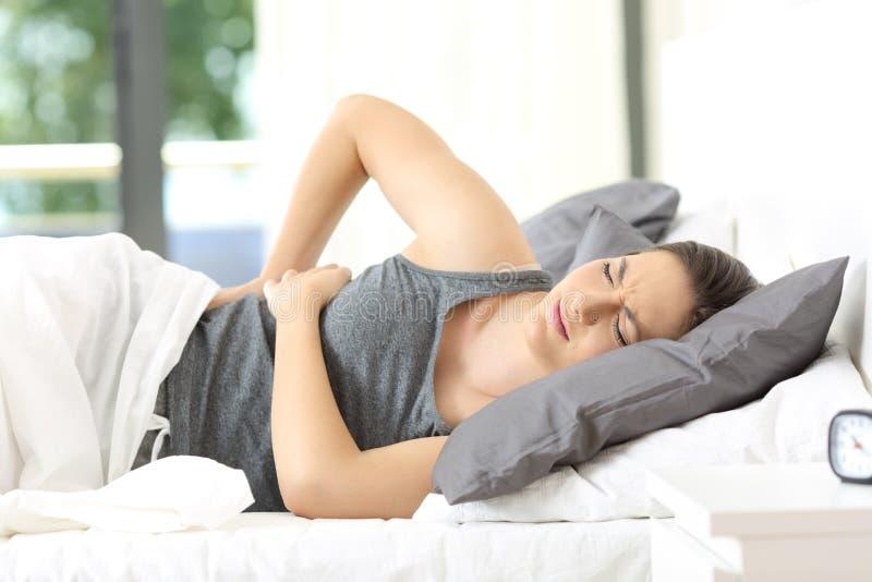 叫醒遭受的后背疼痛的妇女 免版税库存照片