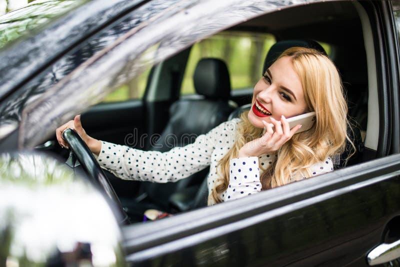 叫年轻美丽的妇女电话,当驾驶在街道上时的汽车 库存照片