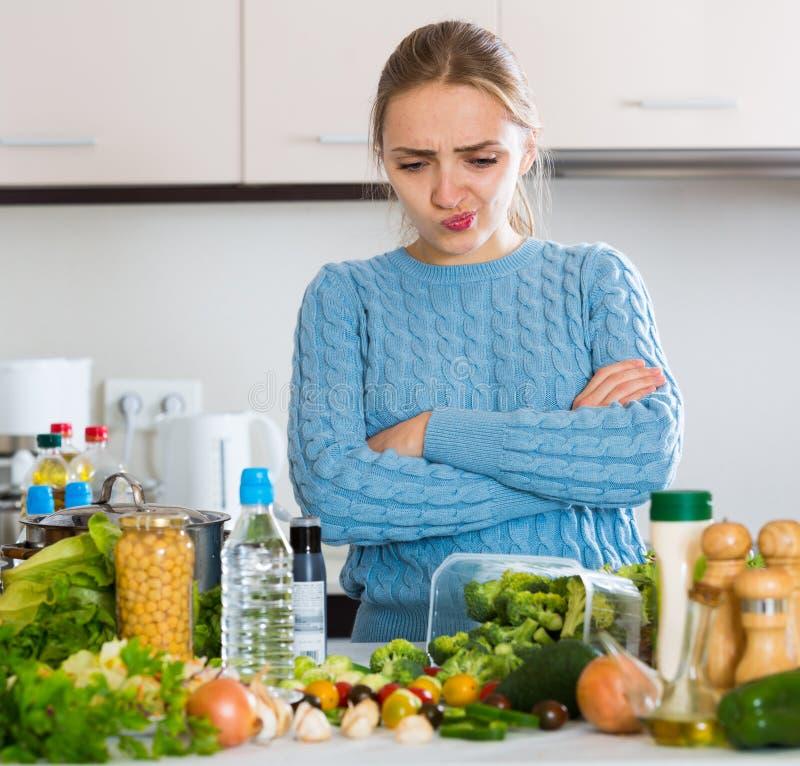 召回晚餐的迷茫的少妇食谱在厨房里 库存图片
