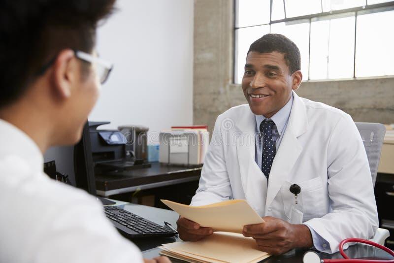 召开文件住院病人会议的混合的族种男性医生 库存照片