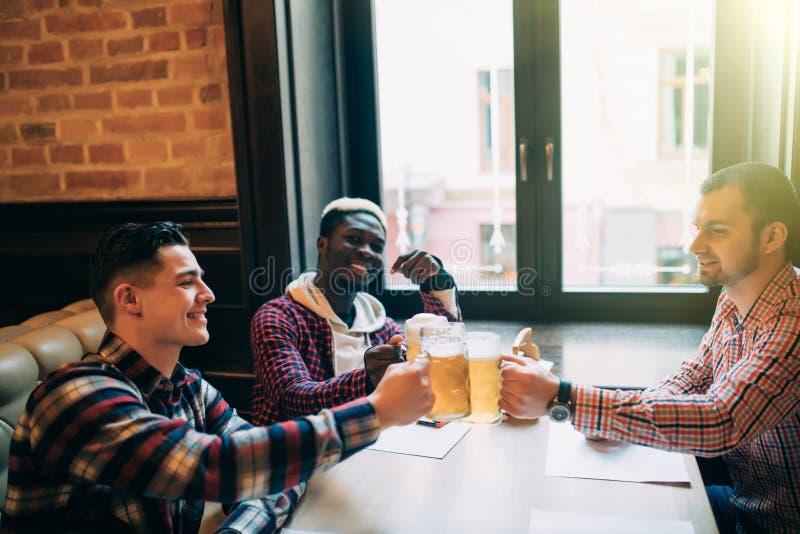 叮当响与啤酒杯的愉快的微笑的人朋友在客栈 免版税库存图片