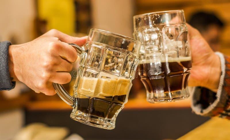叮当响与啤酒杯的愉快的男性朋友在客栈 免版税库存照片
