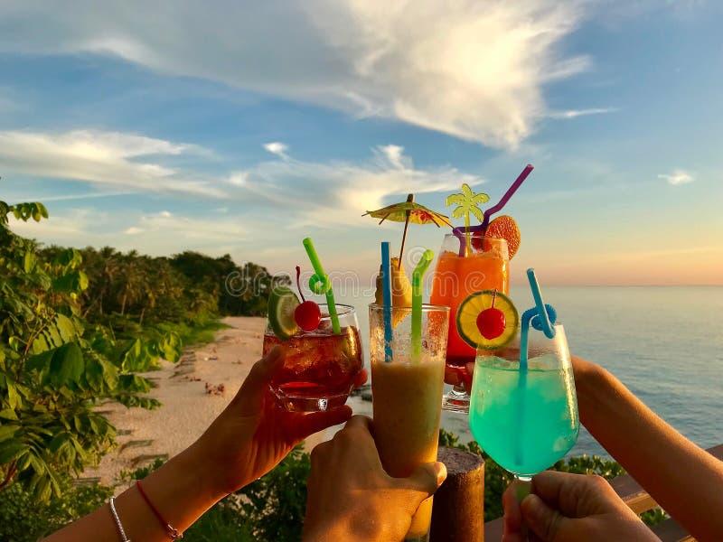 叮当响与在海滩、海和天空背景,夏天热带假期的鸡尾酒杯的手 免版税库存照片