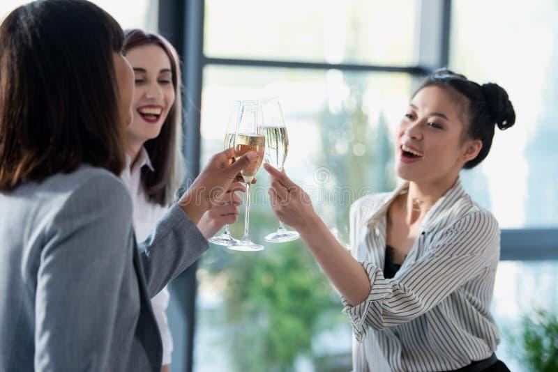 叮当响与香槟玻璃和微笑的Multiethic女实业家 免版税库存图片