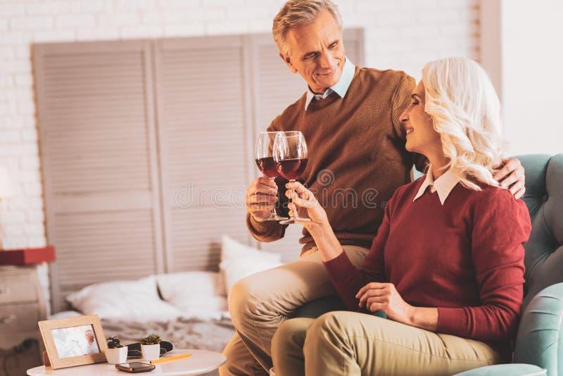 叮当响他们的杯酒的愉快的领抚恤金者夫妇  库存照片