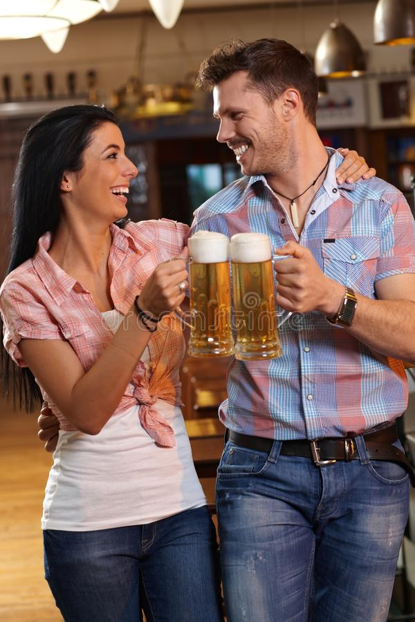叮当响用啤酒的愉快的新夫妇在客栈 免版税库存照片
