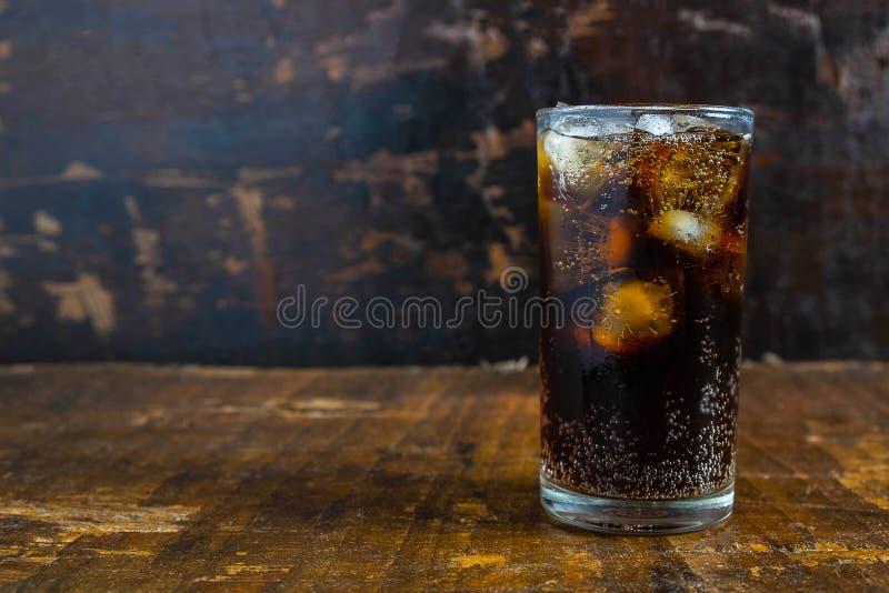 可乐饮料,在一块玻璃的黑汽水在桌上 库存照片