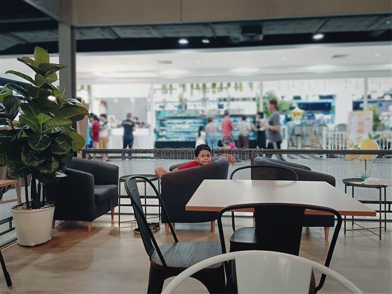 可及在椅子的男孩乏味开会餐馆 图库摄影