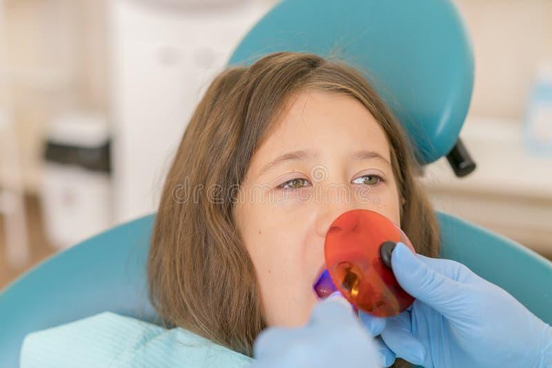 可及牙齿填装的治疗的女孩有紫外技术的槽牙牙 有的女孩的图象她的牙 免版税图库摄影