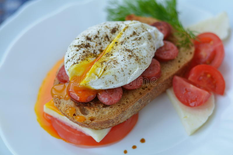 可口三明治用开放荷包蛋,肉,希腊白软干酪,蕃茄,草本,胡椒-在咖啡馆的快速的早餐 免版税库存照片